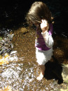 Siena playing in the creek after finishing her smoothie.